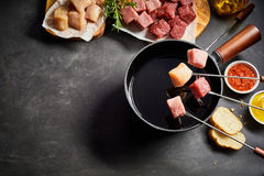 Mixed meat fondue with seasoning and dips. Mixed meat fondue with pork or veal and beef viewed from above with fresh herbs, seasoning and dips on a dark grey royalty free stock photography