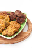 Mixed meat on a plate and kitchen wooden board Royalty Free Stock Image