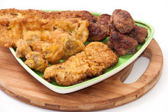 Mixed meat on a plate and kitchen wooden board Stock Image
