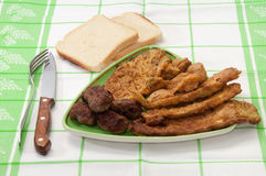 Mixed meat served with bread and a knife and fork Royalty Free Stock Photo