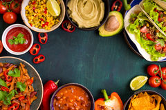 Mixed mexican food background. Party food. Guacamole, nachos, fajita, meat tacos, salsa, peppers, tomatoes on a wooden table. Space for text. Top view. Tex-mex Royalty Free Stock Photo