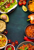 Mixed mexican food background. Party food. Guacamole, nachos, fajita, meat tacos, salsa, peppers, tomatoes on a wooden table. Space for text. Top view. Tex-mex Royalty Free Stock Image