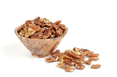 Mixed Nuts. Wooden bowl overflowing with a selection of mixed nuts Stock Photography