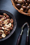 Mixed nuts in basket and nut cracker from above Stock Images