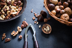 Mixed nuts in basket and nut cracker from above Stock Photography