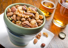 Mixed Nuts and Beer. A bartop bowl of mixed nuts including walnuts, pistachios, almonds, cashews, and hazelnuts Stock Image