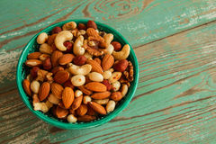 Mixed nuts in a blue bowl on a wooden background. Stock Photos