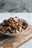 Mixed nuts in bowl. Assorted nuts in white bowl on wooden surface royalty free stock images