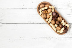 Mixed nuts in a bowl on a white wooden background. Copy space Stock Photography