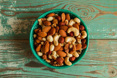 Mixed nuts in a bowl on a wooden background. Royalty Free Stock Photos