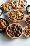 Mixed nuts in bowls. Assorted nuts in bowls on marble surface Royalty Free Stock Photography