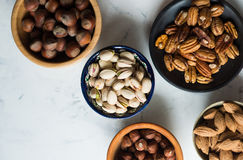 Mixed nuts in bowls. Assorted nuts in bowls on marble table, view from above stock photo