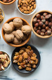 Mixed nuts in bowls. Assorted nuts in wooden bowls on marble table, view from above Royalty Free Stock Photography