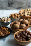 Mixed nuts  in bowls on marble table. Assorted nuts in bowls on marble surface Royalty Free Stock Photo