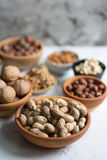 Mixed nuts  in bowls on marble table. Assorted nuts in wooden bowls on white surface, peanuts in focus Royalty Free Stock Images