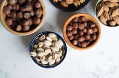 Mixed nuts  in bowls on marble table. Assorted nuts in bowls on marble table, view from above Stock Image