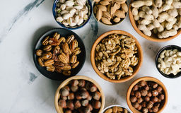 Mixed nuts  in bowls on marble table. Assorted nuts in wooden bowls on marble table, view from above Royalty Free Stock Photos