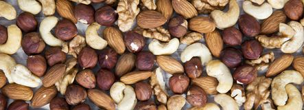 Mixed nuts cashew, hazelnuts, walnuts, almonds on white wooden surface, top view. From above, overhead. Mixed nuts cashew, hazelnuts, walnuts, almonds on white royalty free stock image