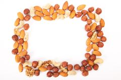 Mixed nuts and dry fruits frame. On white background royalty free stock image