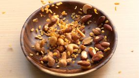 Mixed Nuts fall into a wooden plate on the table