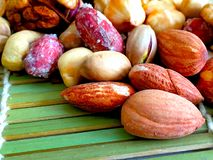 Mixed nuts on a green bamboo tablecloth royalty free stock photography