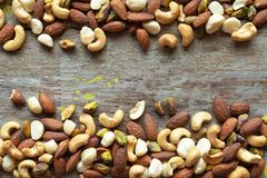 Mixed nuts healthy snack frame on wooden background. Stock Photos