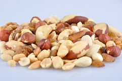 Mixed nuts. Heap of mixed nuts isolated on light blue background stock image