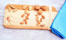 Mixed Nuts like almonds peanuts and walnuts. Mixed nuts like walnuts peanuts and almonds. Nuts some opened some in shells on  wooden cutting board on a blue Stock Photo
