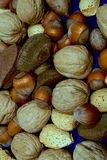 Mixed nuts mingling. On blue surface Stock Photo