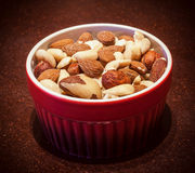 Mixed nuts in red bowl. On wooden table Royalty Free Stock Images