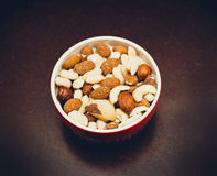 Mixed nuts in red bowl. On wooden table Stock Photography