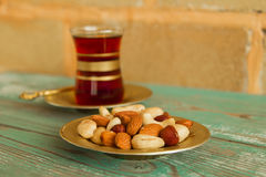 Mixed nuts on a saucer and a glass cup of Turkish tea on a turquoise wooden table on the background of a brick wall. Royalty Free Stock Photo