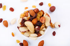 Mixed nuts and sultanas on a plate on a white background Stock Photography