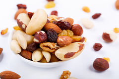 Mixed nuts and sultanas on a plate on a white background Royalty Free Stock Image