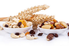 Mixed nuts and sultanas on a plate on a white background Stock Photo