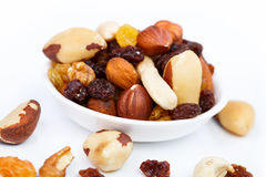 Mixed nuts and sultanas on a plate on a white background Stock Photos