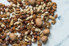 Mixed nuts on table. Assorted nuts on white surface Royalty Free Stock Images