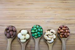Mixed nuts in wood spoon on wood background Stock Photos