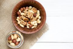 Mixed nuts in wooden bowl on the white wooden table. Background, copy space, top view, close up royalty free stock photos