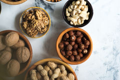 Mixed nuts in wooden bowls. Assorted nuts in wooden bowls on marble table, view from above Stock Photo