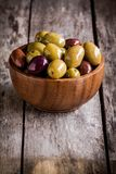Mixed olives in a bowl on a rustic table. Mixed olives in a wooden bowl on a rustic table Royalty Free Stock Photo