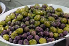 Mixed olives sprinkled with herbs in a white bowl Royalty Free Stock Photography
