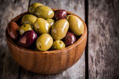 Mixed olives in a wooden bowl closeup on a rustic table. Mixed olives in a wooden bowl on a rustic table Royalty Free Stock Photos