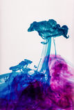 Mixed paint in water. Blue and purple color royalty free stock photo