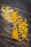 Mixed the pasta with spaghetti on wooden background. Top view Royalty Free Stock Photos