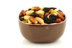 Mixed peanuts and raisins in a brown bowl Stock Images