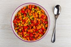 Mixed pepper, carrot, green peas, corn in ceramic bowl, spoon on table. Top view royalty free stock photography