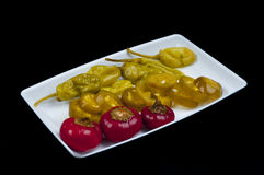 Mixed pepper pickles. On the white plate Stock Photography
