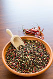 Mixed peppercorns in bowl. Colored peppercorns in ceramic bowl with hot chillies on background royalty free stock photos