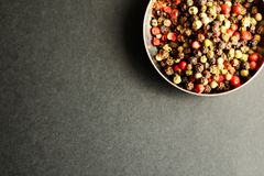 Mixed peppercorns. In the bowl on grey background Royalty Free Stock Images